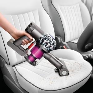 Handstaubsauger mit Bürste wird im Auto eingesetzt